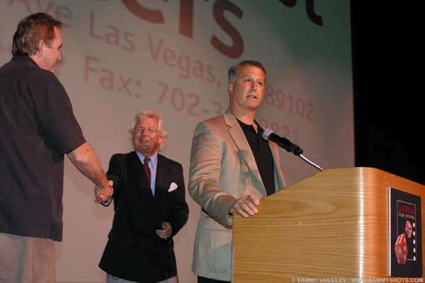 Our client Rick Brandelli accepting his First Place Script Award at the Las Vegas Film & TV Festival. His script was written by our head writer Wayne Carter, left, who joined him on stage.