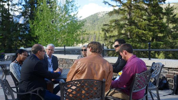 Breakthrough Entertainment President Nat Abraham (dark suit and dark hair) and Breakthrough CFO, Michael McGuigan (dark suite, light hair) meets with Hit Maker Tour members last summer amid spectacular Banff scenery.